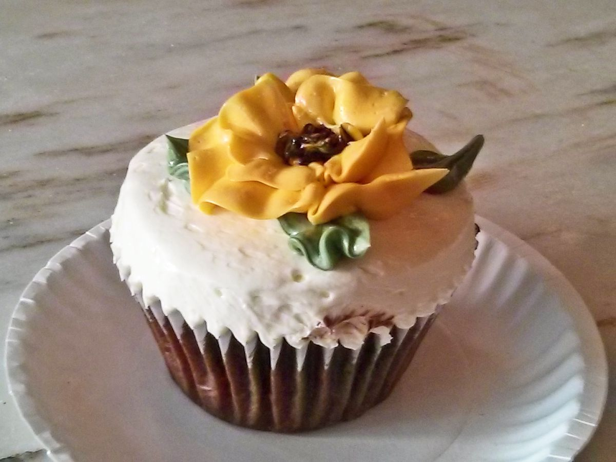 A cupcake with white icing and a yellow flower in top.
