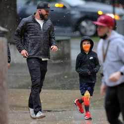 Fans run in the rain as they arrive to watch the Utah Jazz and the Memphis Grizzlies play in game one of their NBA playoff series at Vivint Arena in Salt Lake City on Sunday, May 23, 2021.