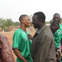 Yeah Samake, center, talks with villagers while campaigning to become mayor of a region in Africa. Samake has a master's degree from BYU.