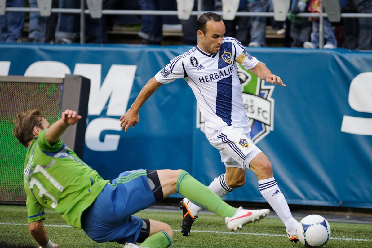 May 2, 2012; Seattle, WA, USA; Los Angeles Galaxy midfielder Landon Donovan (10) chases the ball as Seattle Sounders FC defender Jeff Parke (31) slide tackles during the first half at CenturyLink Field. Mandatory Credit: Steven Bisig-US PRESSWIRE