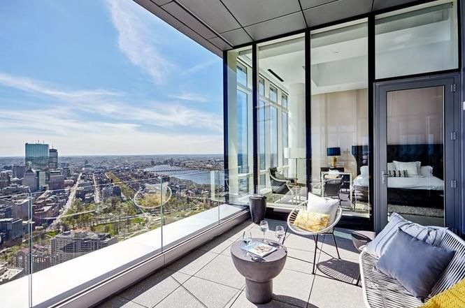 The terrace of a high-rise condo with furniture and wide city views.