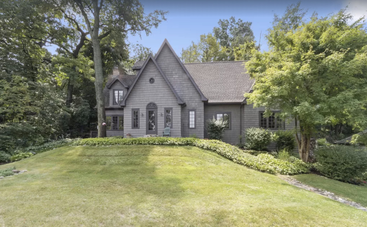 A home with asymmetrical gables, a grassy front yard, and a grey-black exterior.