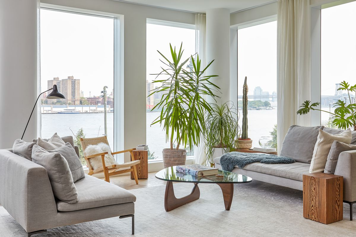 A living area with couches, an arm chair, glass table, and planters with plants. There are floor to ceiling windows overlooking a waterfront and buildings in the distance.