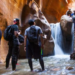 ADVANCE FOR WEEKEND EDITIONS - In this June 6, 2017, photo, a group of friends wait at the bottom of the Kanarraville Falls while another group comes down the ladder, on the outskirts of Kanarraville, Ore. For years, Kanarraville Falls was one of Southern Utah's best-kept secrets. The hidden hike leading to a slot canyon waterfall was seemingly reserved for residents of the small town of Kanarraville. (/The Spectrum via AP)
