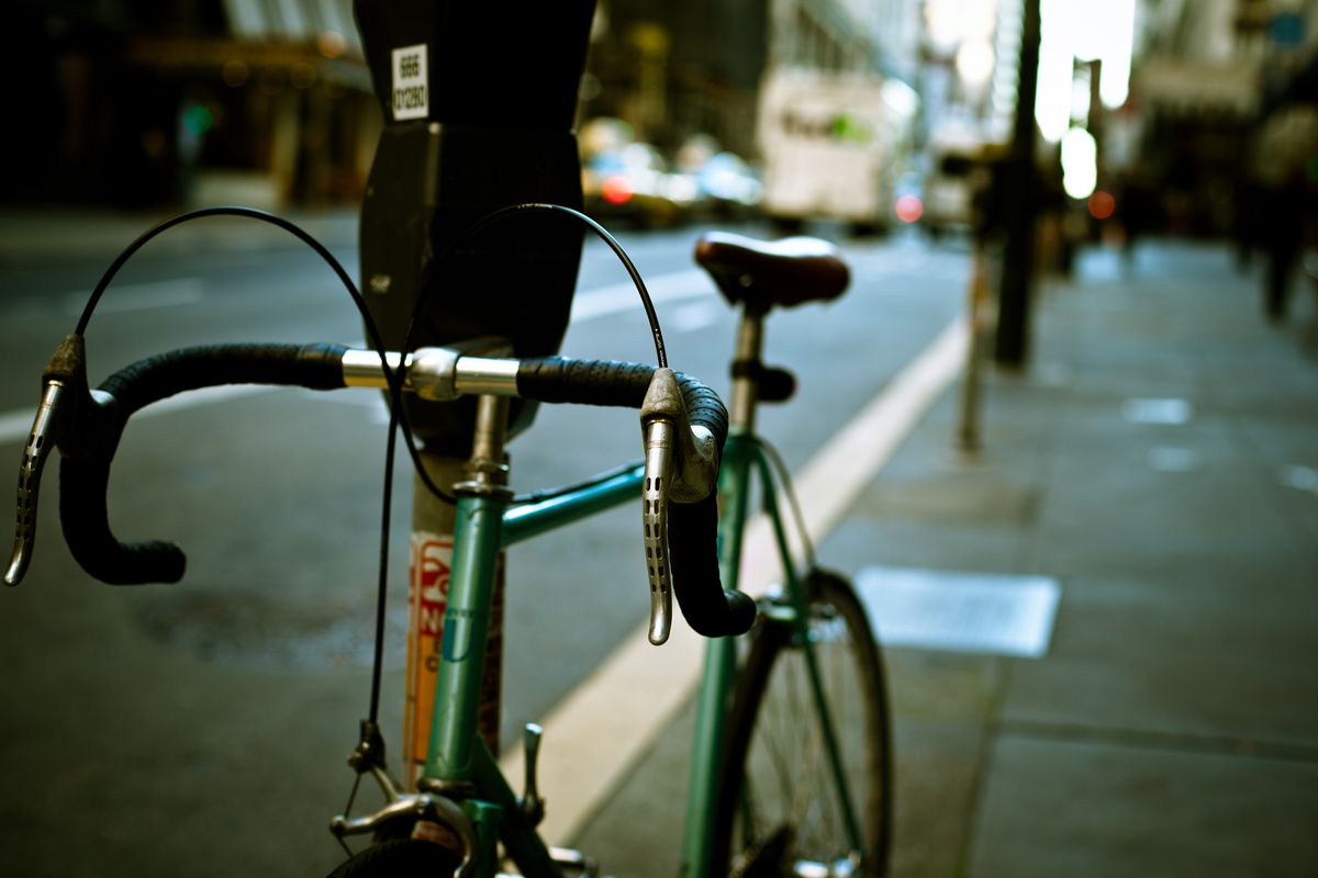 A green bicycle attached to a parking meter on a sidewalk in San Francisco.
