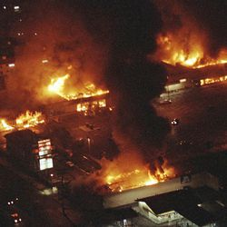 FILE - This April 29, 1992 file photo shows several buildings in a Boys Market shopping center fully engulfed in flames before firefighters can arrive as rioting erupted in South-Central Los Angeles. The acquittal of four police officers in the videotaped beating of Rodney King sparked rioting that spread across the city and into neighboring suburbs. Cars were demolished and homes and businesses were burned. Before order was restored, 55 people were dead, 2,300 injured and more than 1,500 buildings were damaged or destroyed.