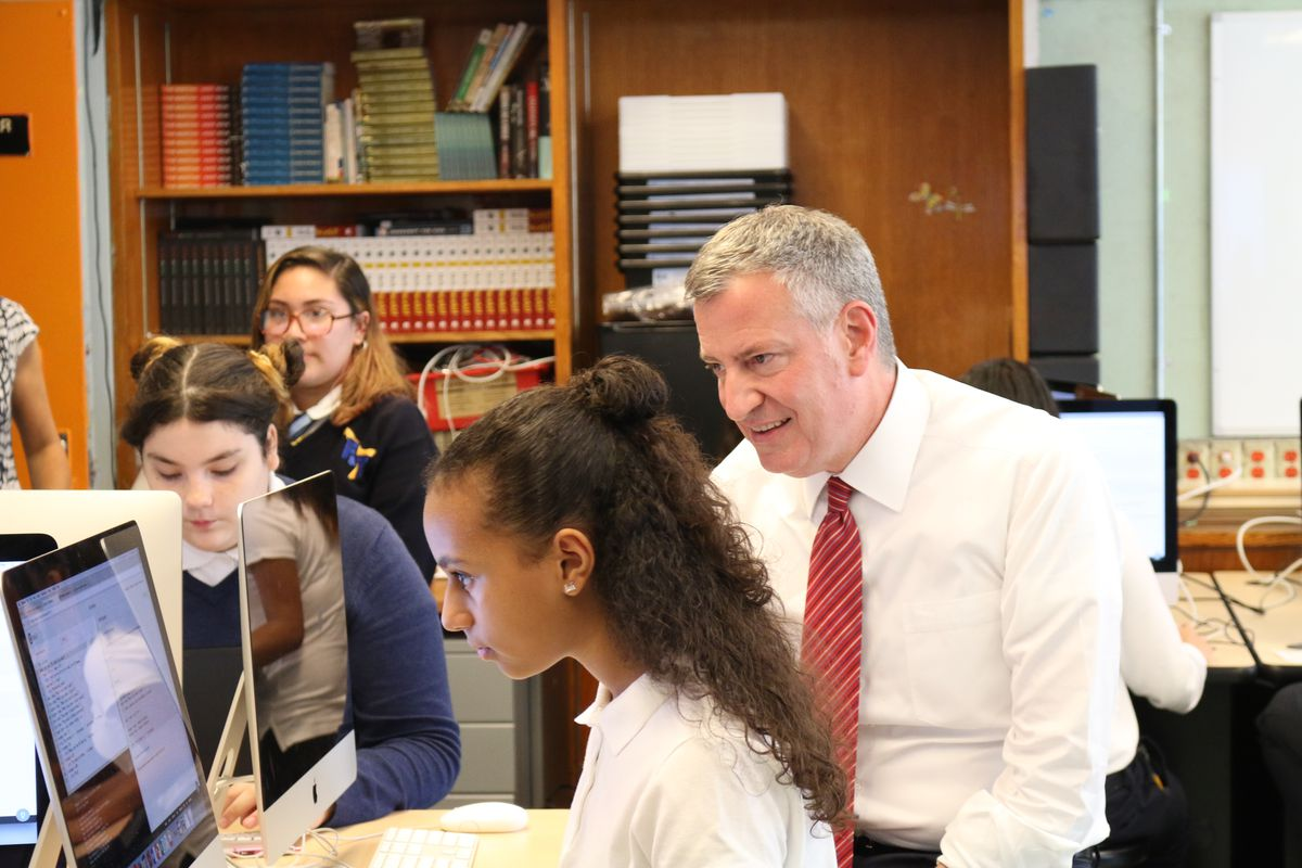 Mayor Bill de Blasio learns about computer science from a student at the Laboratory School of Finance and Technology in the Bronx