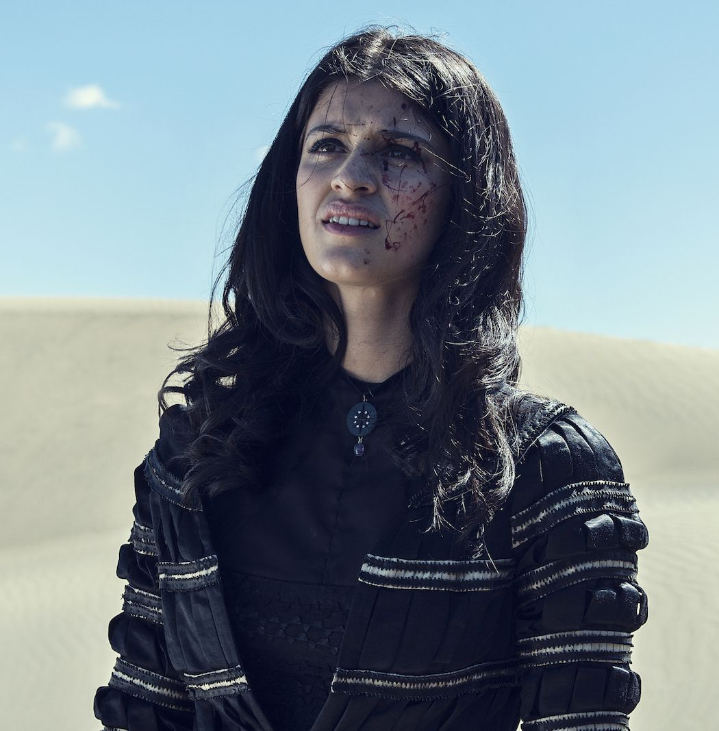 yennefer standing in a black dress in a desert with blood on her face