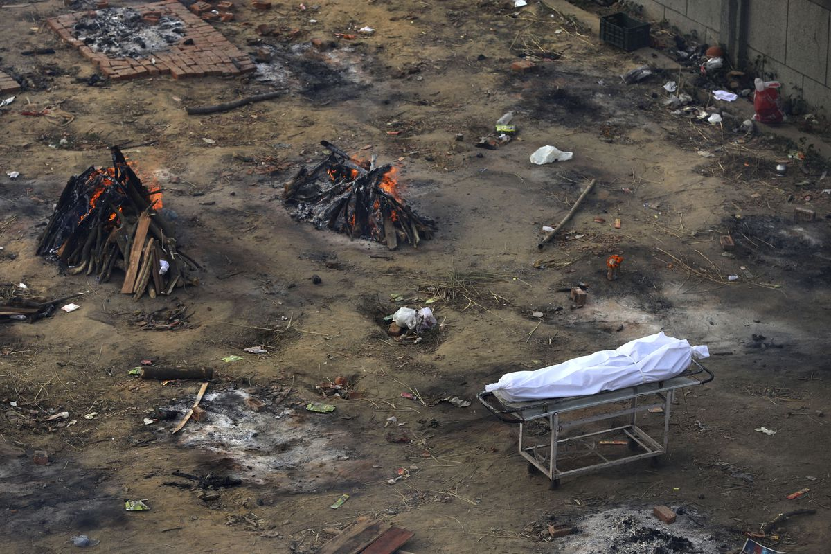 Multiple funeral pyres of those patients who died of COVID-19 disease are seen burning at a ground that has been converted into a crematorium for mass cremation of coronavirus victims, in New Delhi, India, Wednesday, April 21, 2021.
