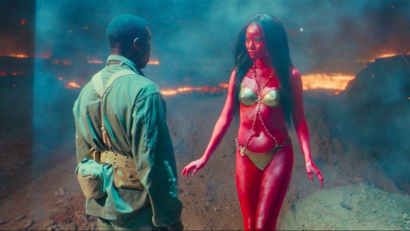 A soldier stands facing a red-skinned woman in a bikini.