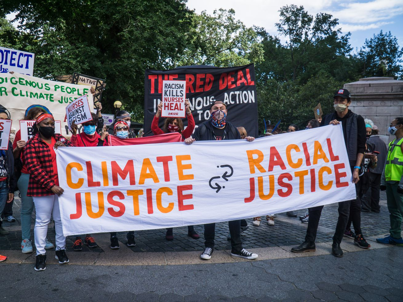 """Protesters carrying a banner that reads, """"Climate justice = racial justice."""""""