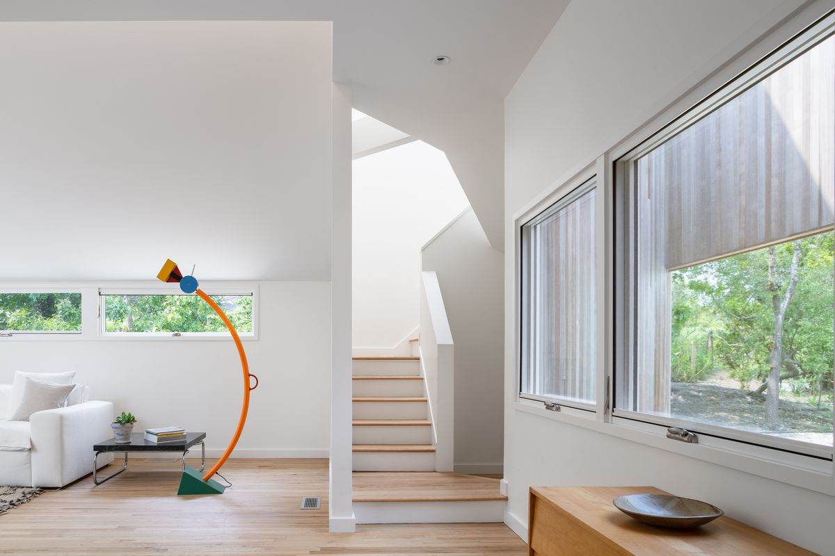 A staircase surrounded by white walls and large rectangular windows.