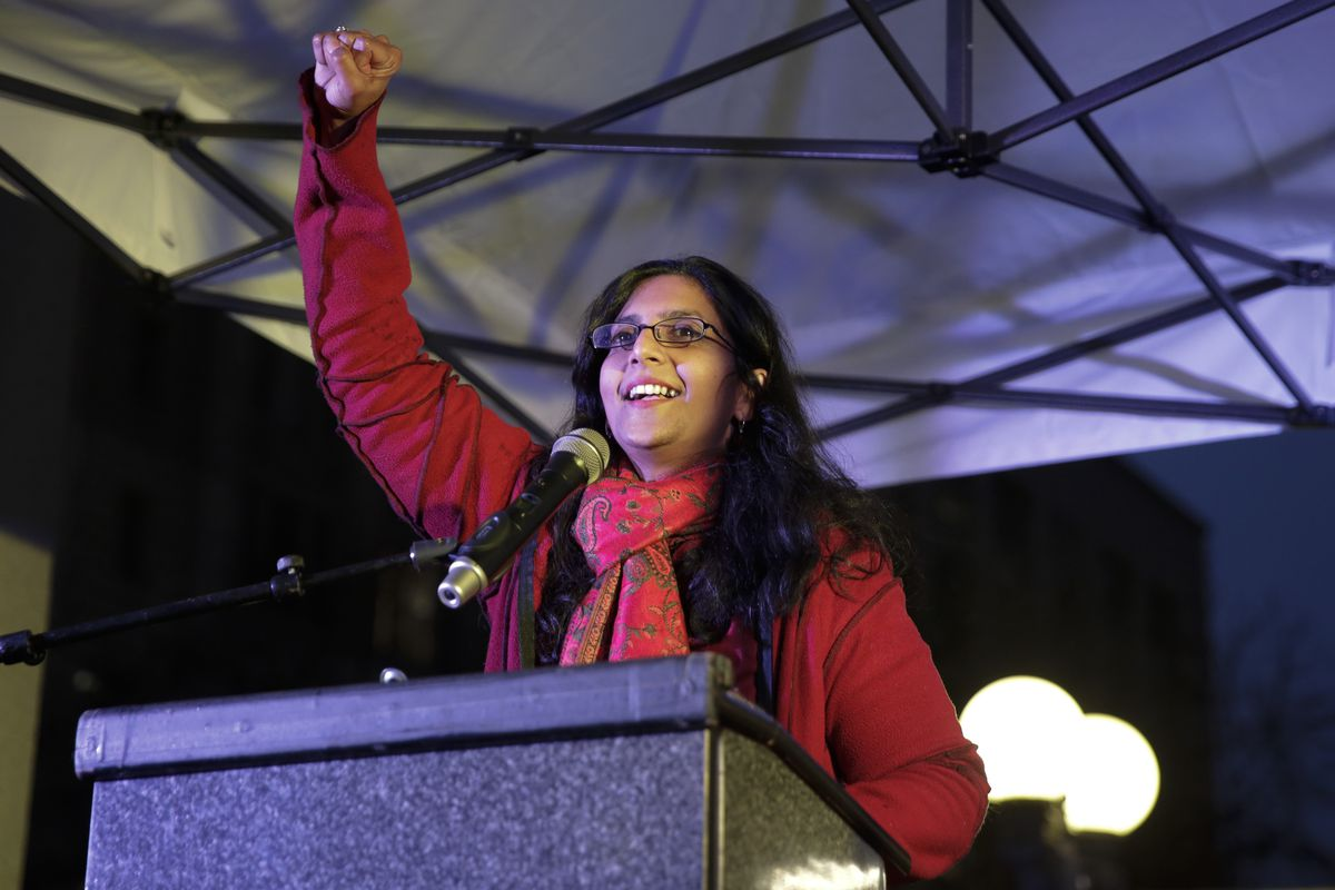 Seattle City Councilmember Kshama Sawant holds up her fist onstage in front of a podium.