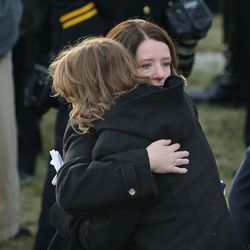 Erika Barney, left, is hugged by her daughter, Merri, at the gravesite of their husband and father, Unified police officer Doug Barneyat the Orem City Cemetery on Monday, Jan. 25, 2016. Barney was killed in the line of duty on Jan. 17, 2016.