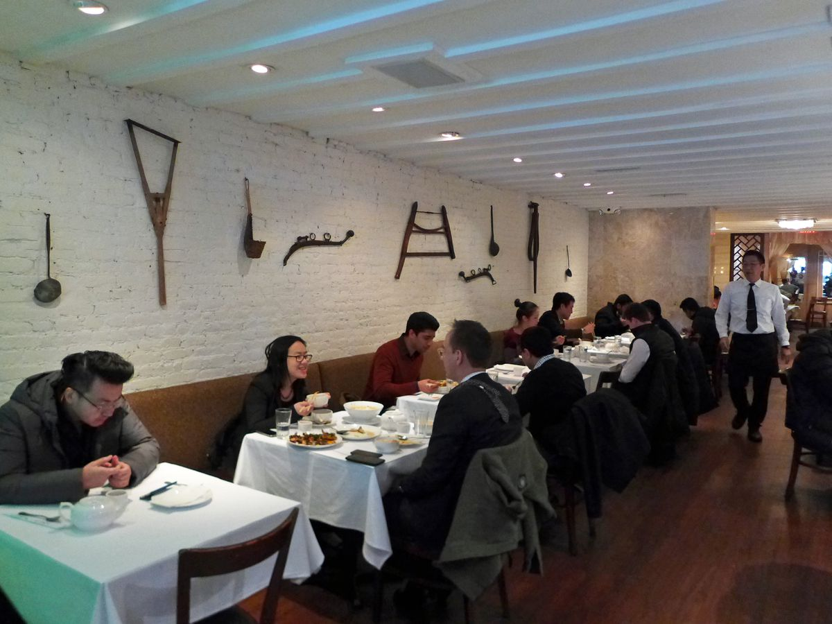 Diners eating and talking at tables with white tablecloths in a white-walled room at Land of Plenty