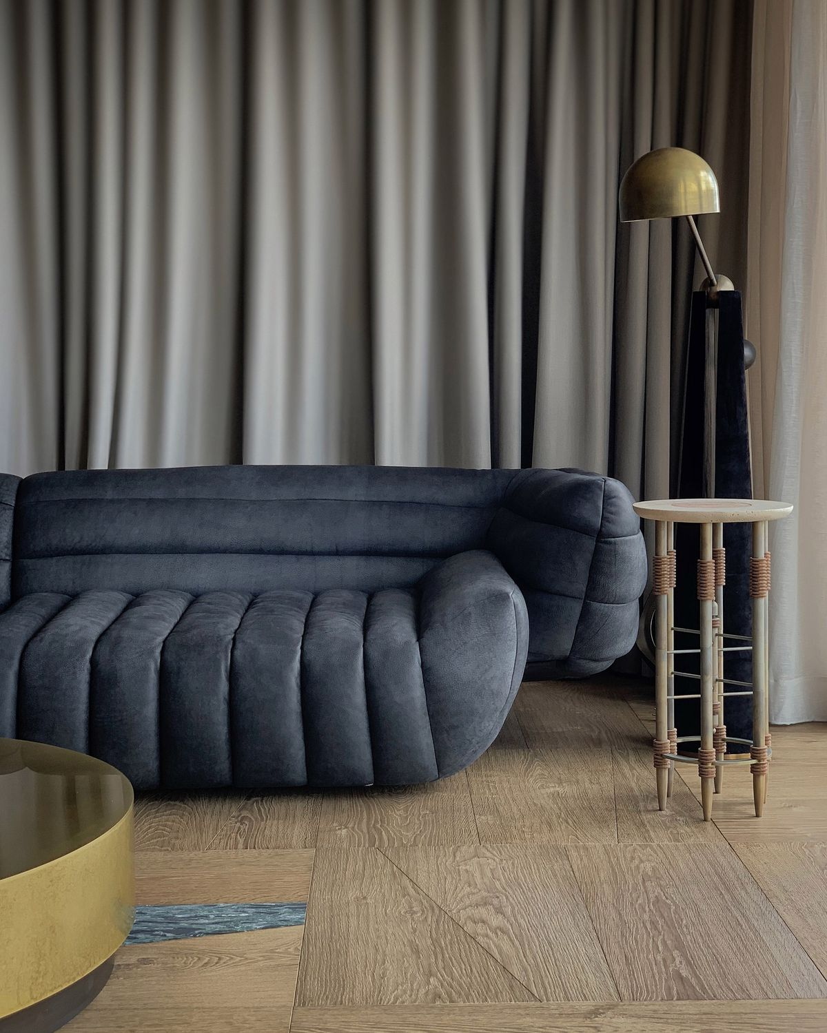 A plush dark gray couch against gray curtains.