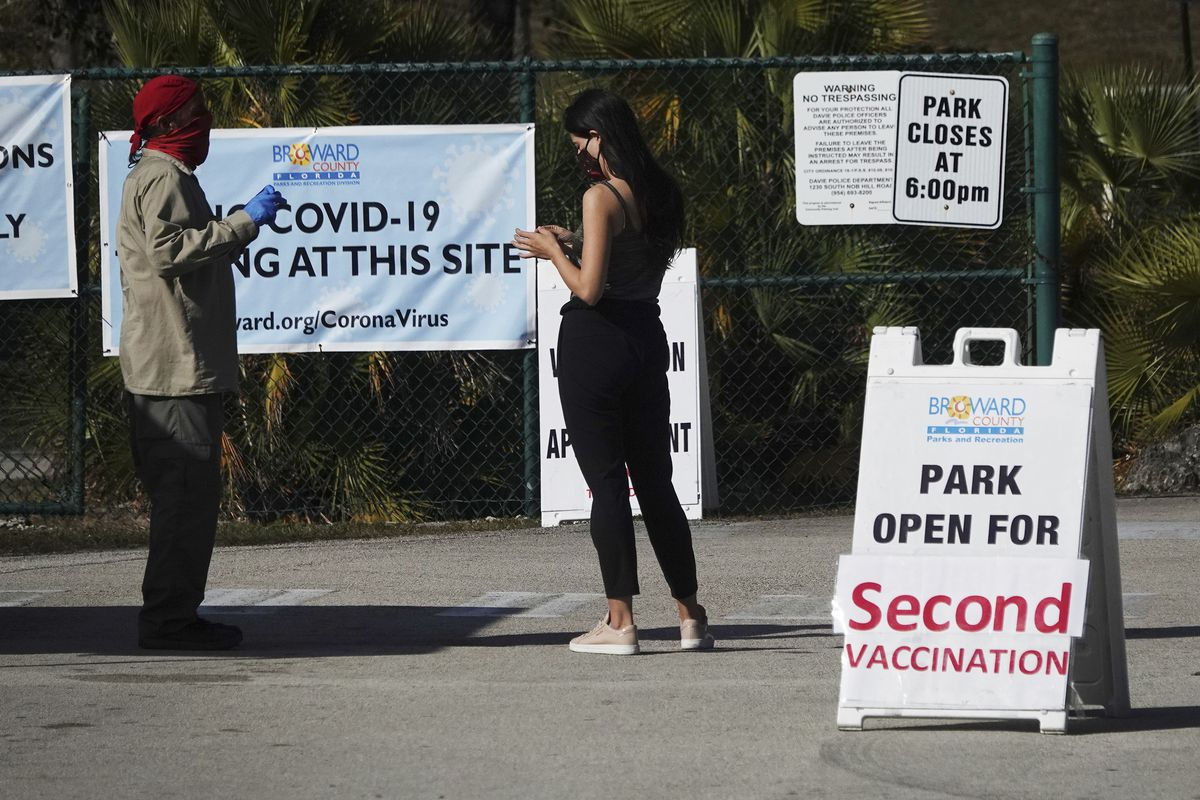 In this Jan. 27, 2021, file photo, woman asks directions at the entrance to Vista View Park where a COVID-19 vaccination site has opened for second doses in Davie, Fla.