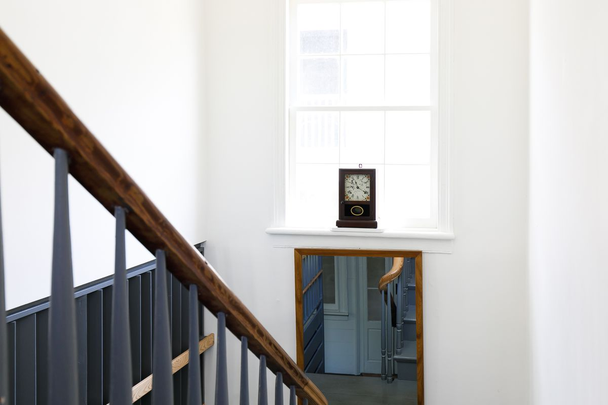 A staircase painted grey leads down towards the first floor of a house. There is a window above the doorway on the first floor letting in bright light from outside.
