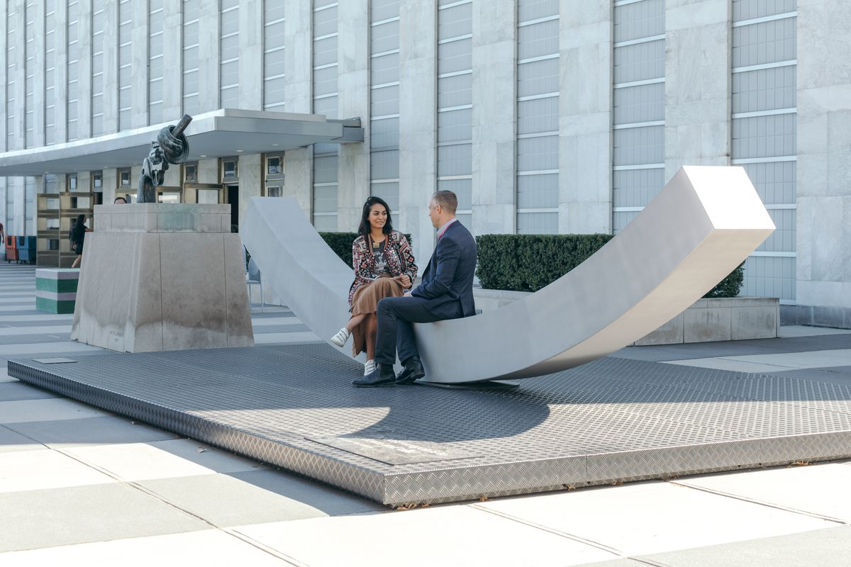 Two people sitting on bench arched upward.
