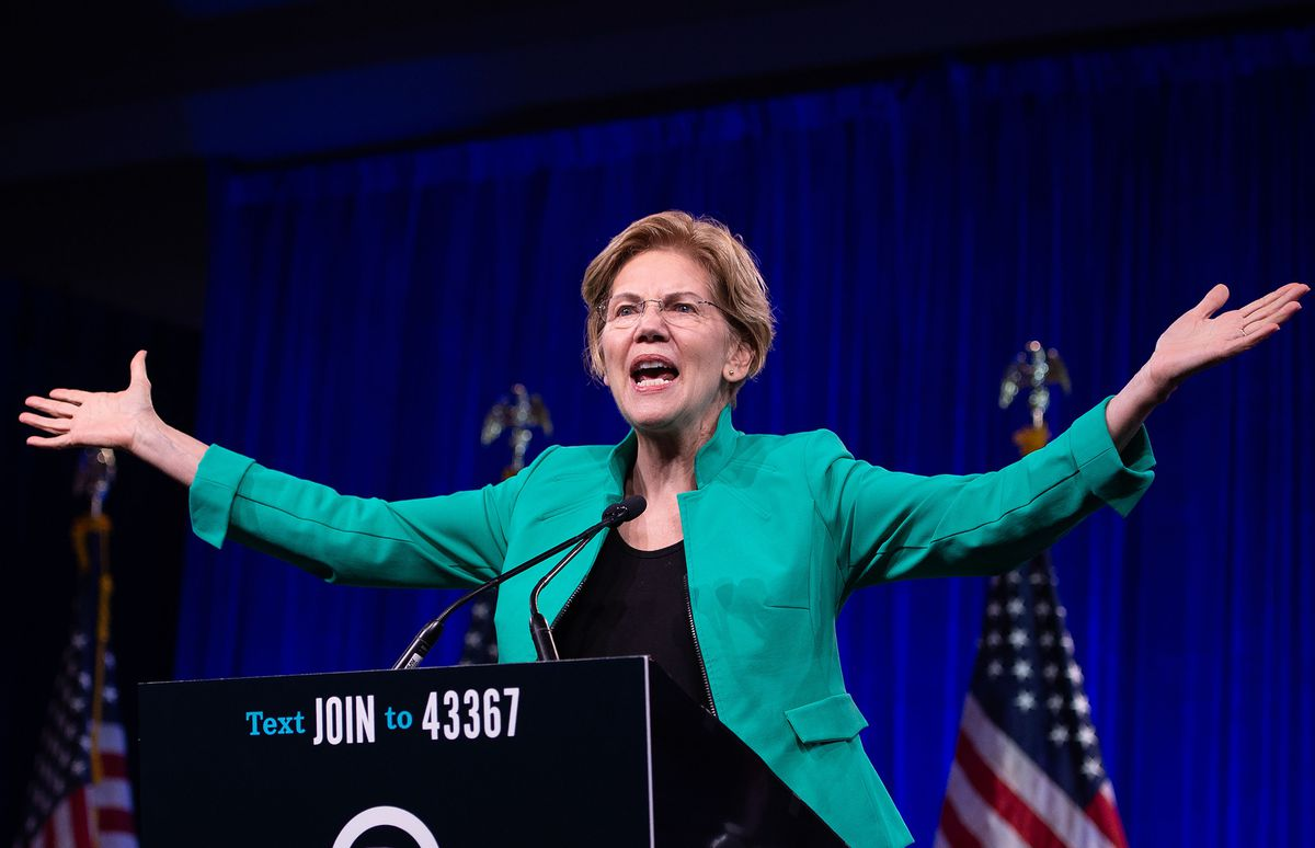 Democratic presidential candidate Elizabeth Warren speaking from behind a podium with her arms raised out to her sides.