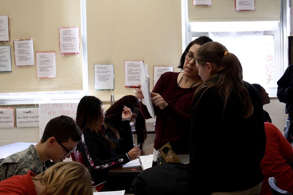 Robin Clark, a math teacher at Manual High School, goes over an assignment with a student.