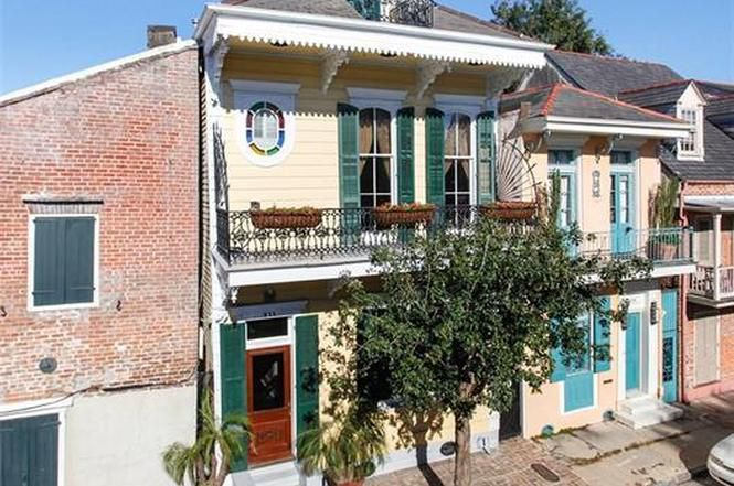 The exterior of 833 Barracks Street in New Orleans. The facade is yellow with green shutters and a balcony on the upper level.