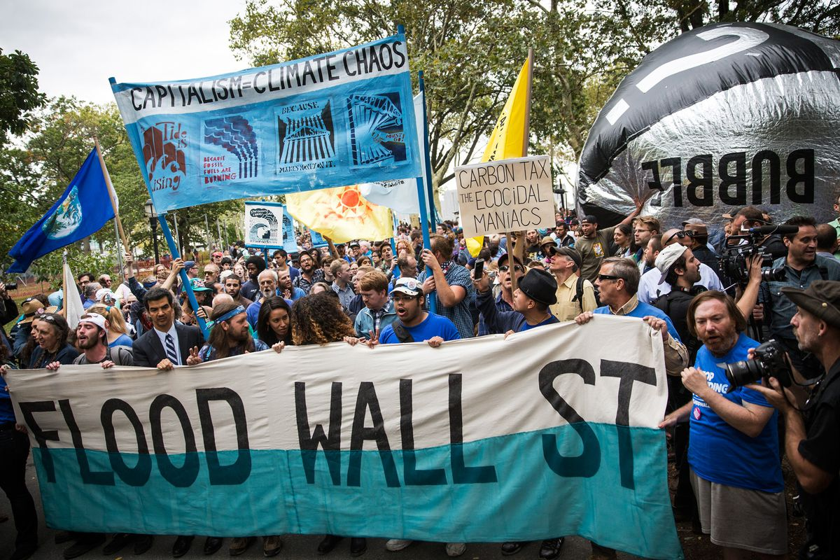 Protesters calling for massive economic and political changes to curb the effects of global warming hold a sit in around the Wall Street Bull statue on Broadway on September 22, 2014 in New York City