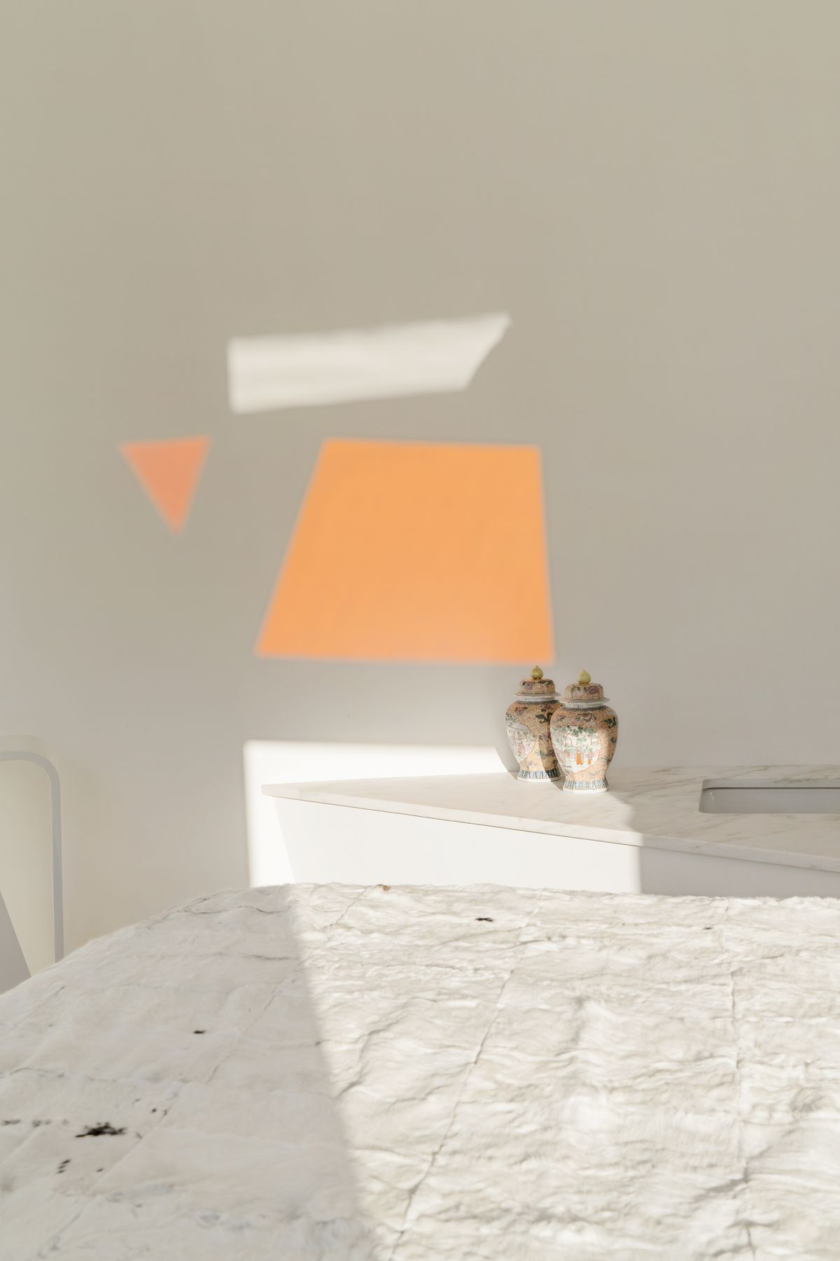A white bed is next to a wide table and white walls. Warm orange reflection is on the wall.