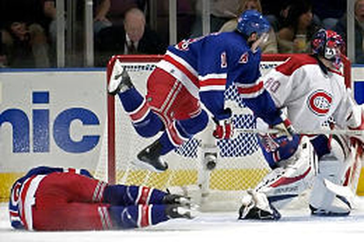 The New York Rangers' Blair Betts leaps over teammate Jason Ward in front of Montreal goaltender Jose Theodore during Monday's game.