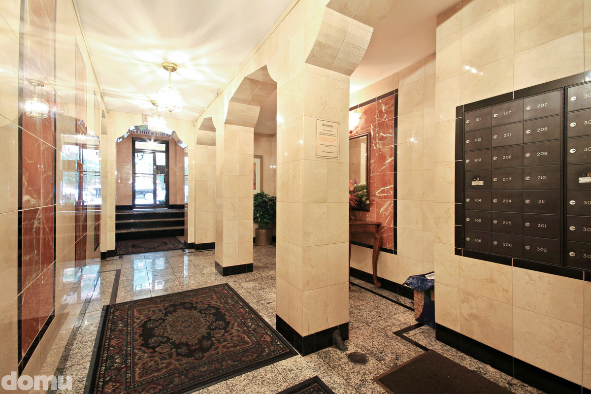 A building entryway with marble walls and black mailboxes on the wall.