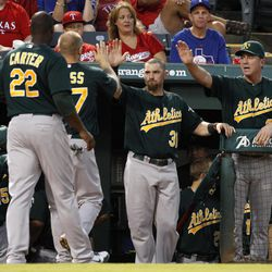 Oakland Athletics' Chris Carter (22) and Brandon Moss are congratulated by Brandon Moss (37) and manager Bob Melvin, right, in the dugout after the two scored on Josh Donaldson's single in the first inning of a baseball game against the Texas Rangers, Wednesday, Sept. 26, 2012, in Arlington, Texas.