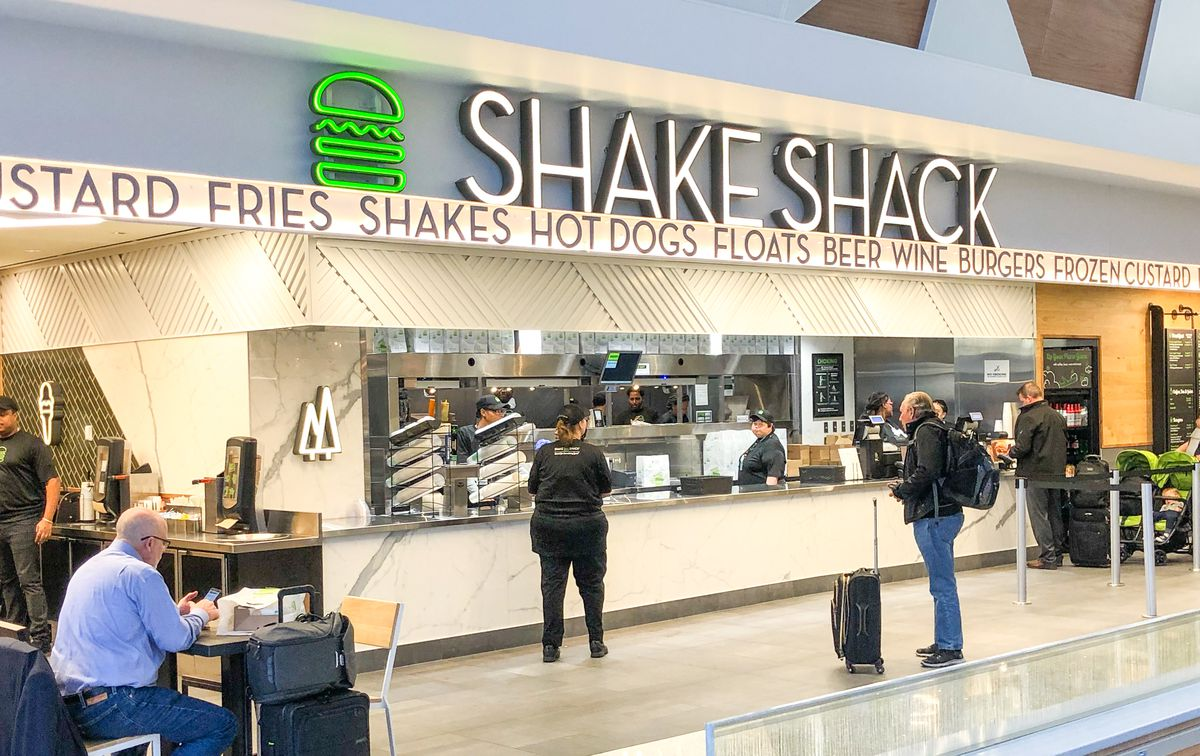 A white fast food stand with the green lit burger logo of Shake Shack