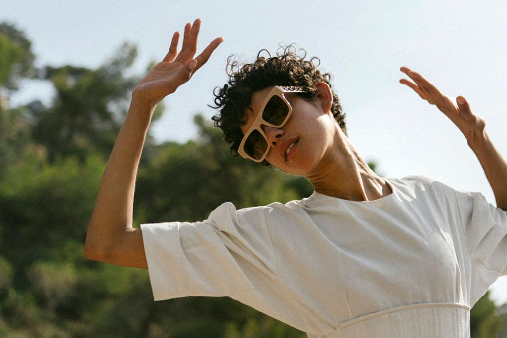 A model wears sunglasses and an off-white top by Stella McCartney