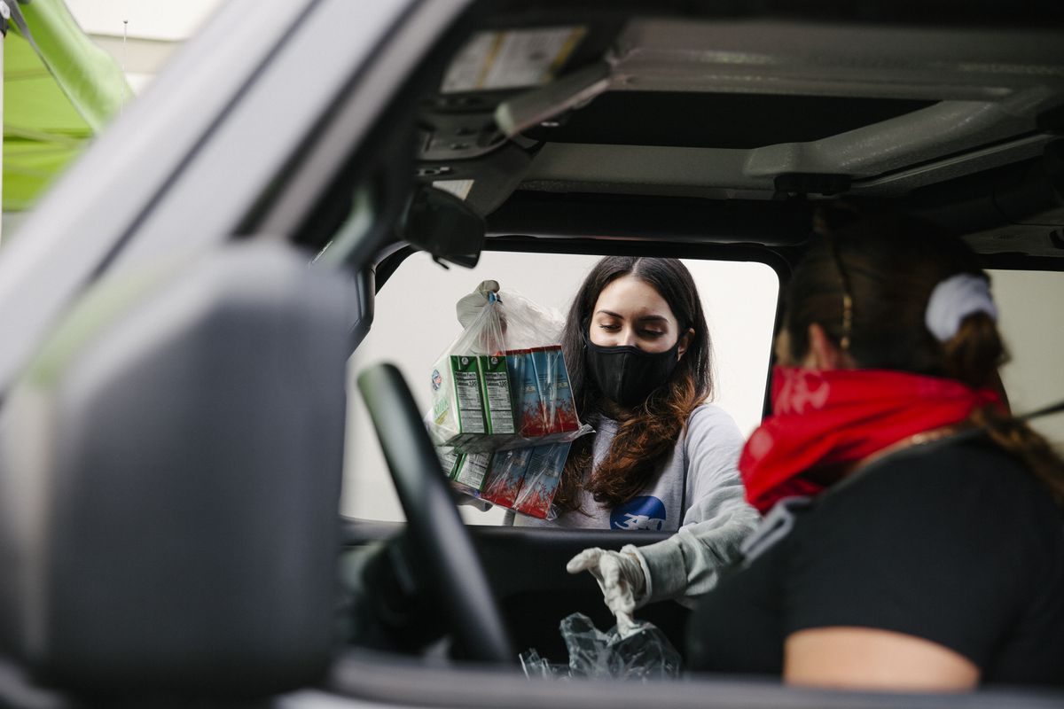 Woman wearing mask hands plastic bag full of juice boxes to another woman seated in the front seat of a car.