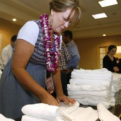 Joni Crane, a Utah delegate from Vernal, Utah folds towels to be put into humanitarian kits in Tampa, Florida.  The Republican National Convention was put on hold because of Hurricane Isaac but the Utah delegates used their extra time to put together humanitarian kits on Monday.  Delegates from Hawaii and Arizona helped out with the 1,000 hygiene kits and 100 back-to-school kits. Monday, Aug. 27, 2012