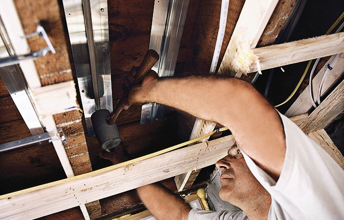 Person using a rubber mallet to tap the PEX into the aluminum track as part of installing radiant floor heating in an existing home.