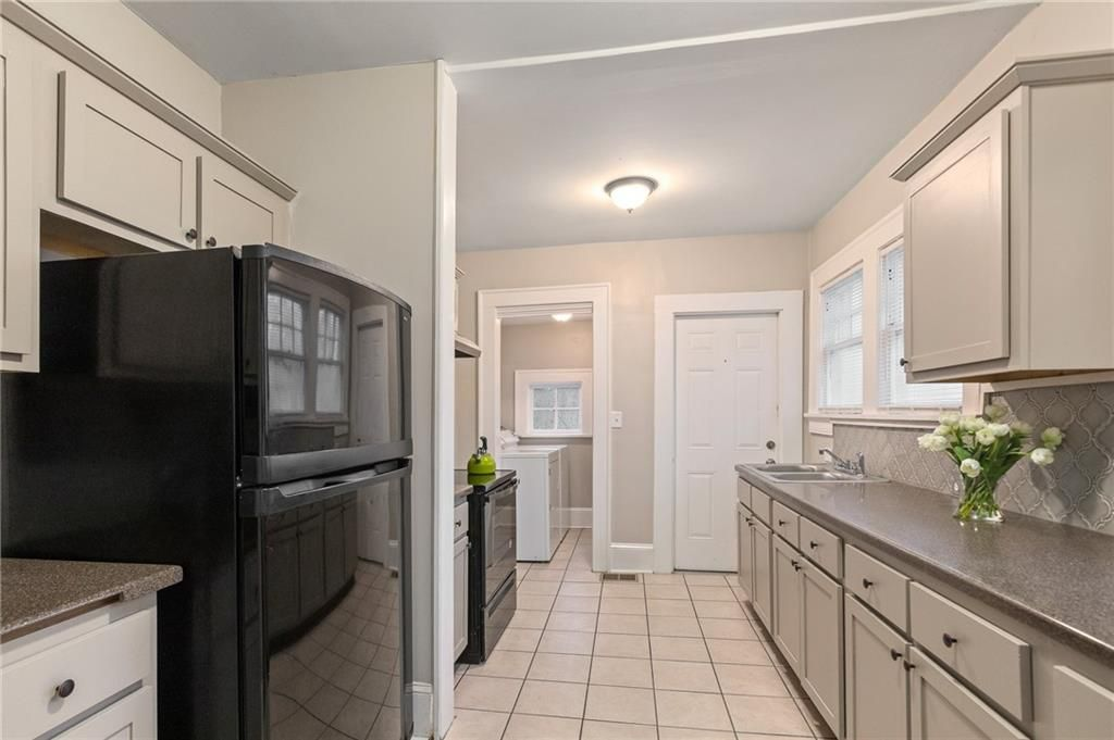 Kitchen with black appliances and tile floors.