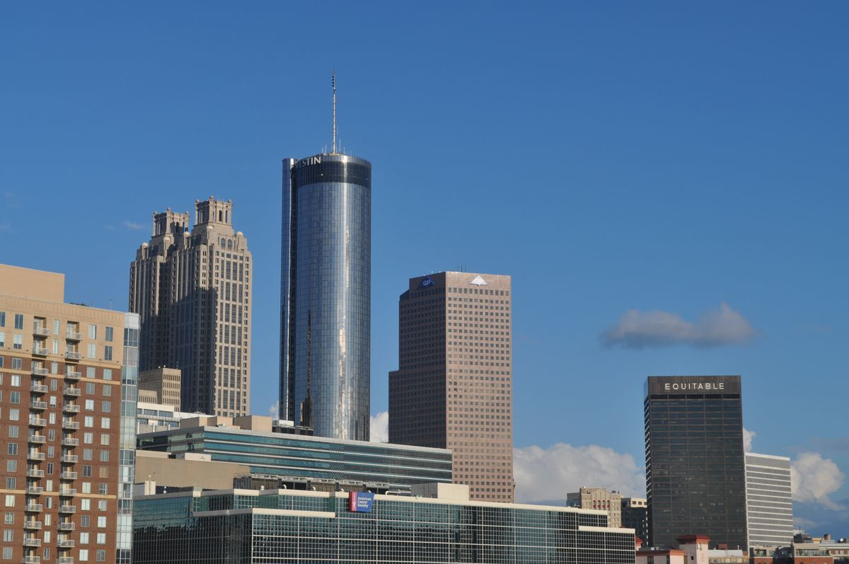 The glassy cylinder of a tall skyscraper surrounded by other buildings.
