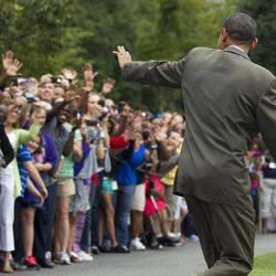 President Barack Obama waves to visitors as he leaves the White House in Washington, Saturday, Sept. 1, 2012,  for a campaign trip.