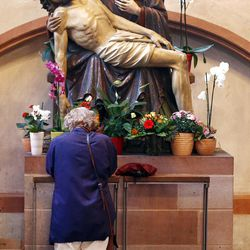 In this photo taken on Thursday, Sept. 27, 2012, a woman prays under a statue depicting Jesus and Mary, in the cathedral of Frankfurt, Germany.