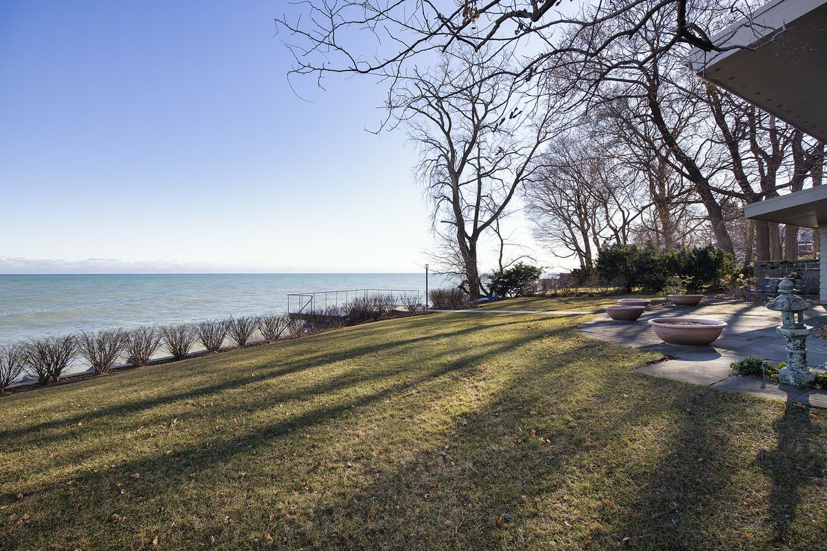 A grassy yard overlooks a large body of water.