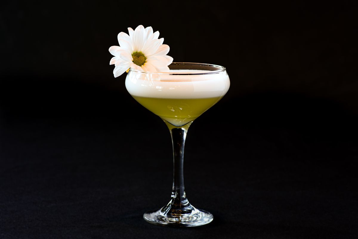 A yellow cocktail with a daisy as a garnish