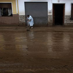 A women cleans a muddy street after flash floods in the town of Villanueva del Rosario, Malaga, southern Spain, Friday, Sept. 28, 2012. Homes were destroyed and at least one woman was killed. Rescue workers are searching to determine if there are more victims.