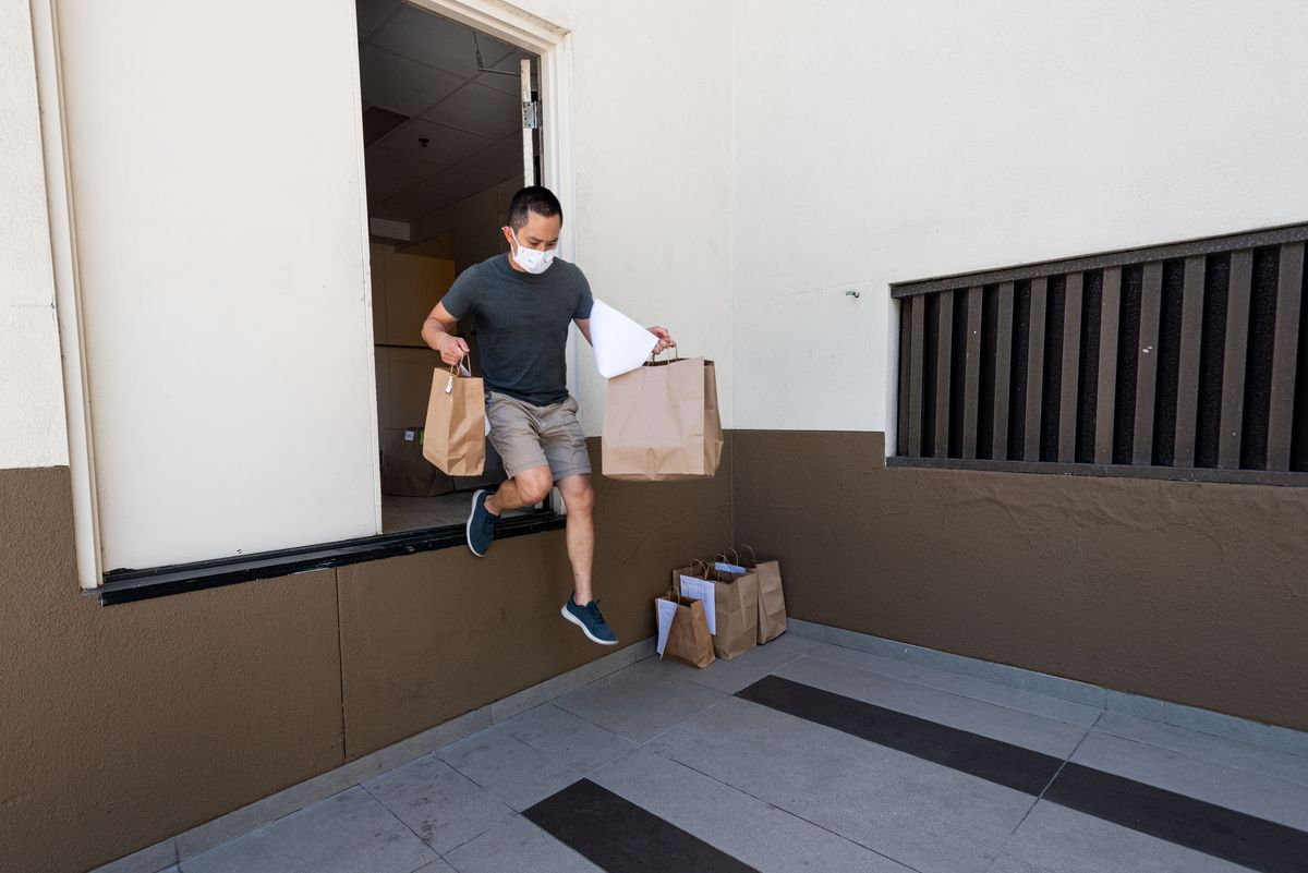 A worker jumps out of a loading dock opening with bags of food in hand.