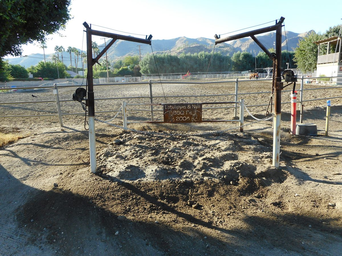 Two metal winches show tow ropes down into the dirt where a covered pit slowly cooks beef underground.