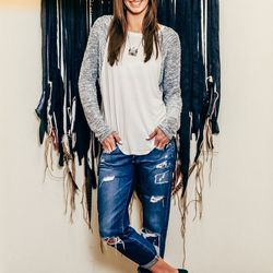 Executive Assistant and Office Manager Brittany Heaps is wearing a Will + Clay shirt, AG jeans, and Vince shoes.