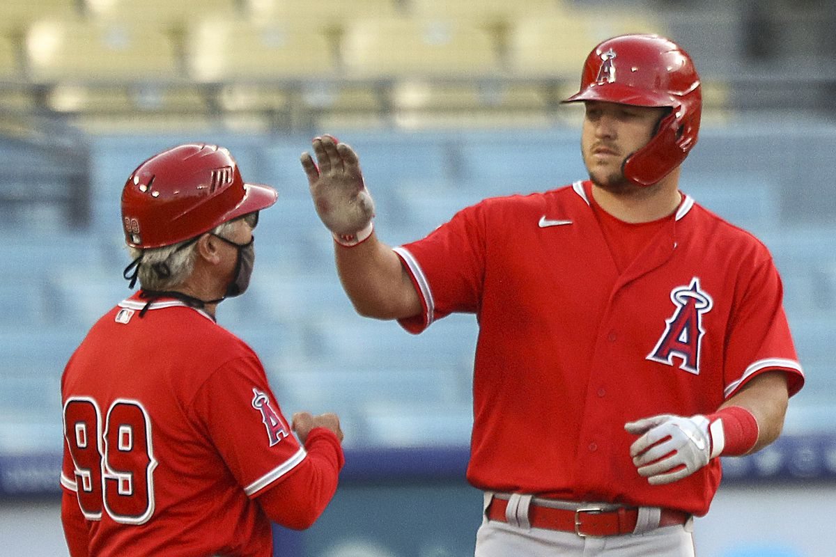 Mike Trout #27 of the Los Angeles Angels reacts with first base coach Bruce Hines #99 during the game against the Los Angeles Dodgers on March 30, 2021 in Los Angeles, California.