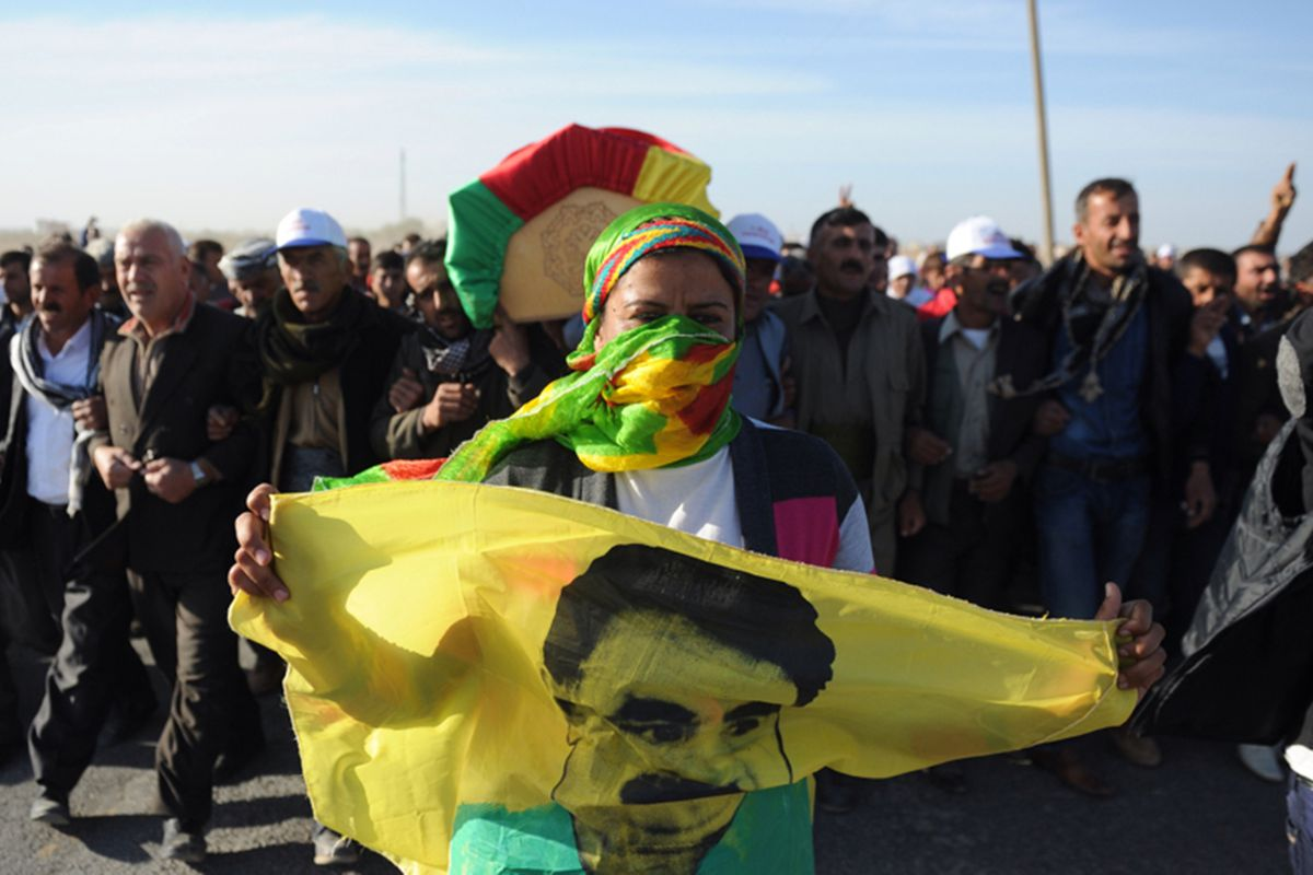 A woman with a flag bearing the face of the PKK's leader, Abdullah Öcalan,  at a funeral for Kurdish fighters who died in Syria.