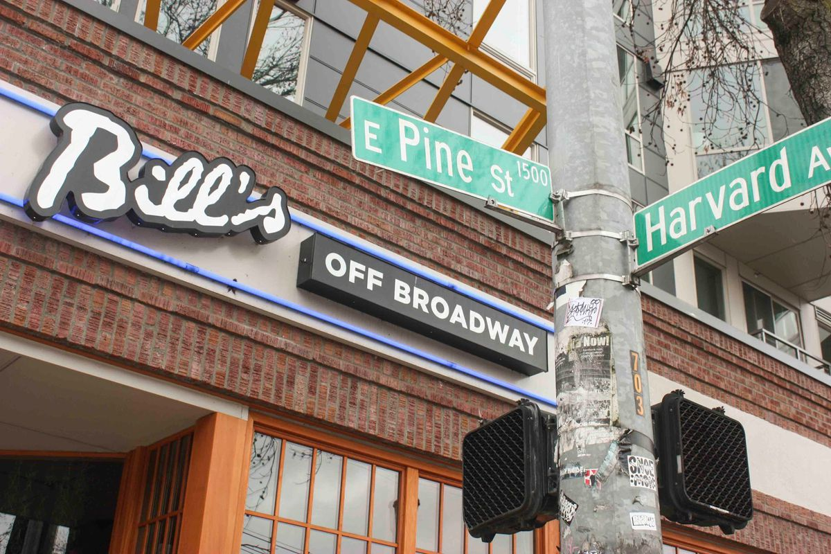 The front of Bill's Off Broadway, with the street signs Pine Street and Harvard Avenue in the foreground