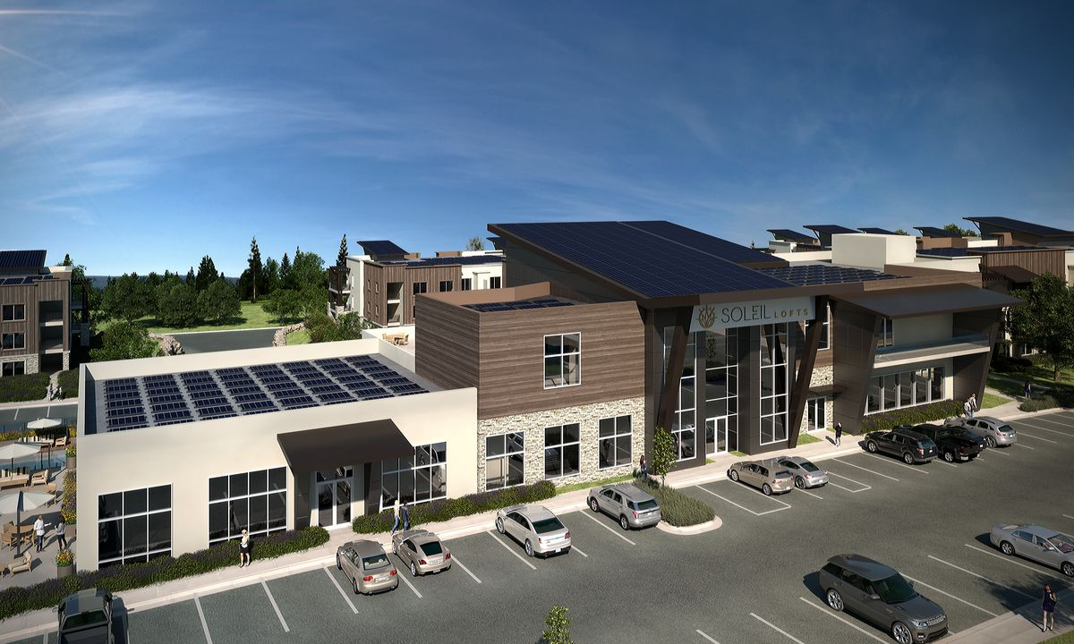 A community center at a forthcoming apartment complex, featuring rooftop solar and stone and wood facades.